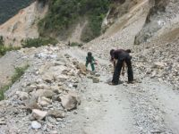 The constant struggle to keep the mountain roads drivable. Here from the road from Banawe to Bontoc in the Mountain province.